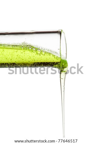 A glass flask with green liquid tilted. The liquid trickling down.