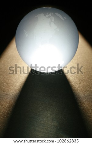 a glass globe in dramatic lighting............