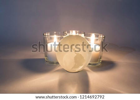A glass globe is illuminated by three candles placed behind it. The focus is on the globe which shows North America, Central America, and South America. #1214692792