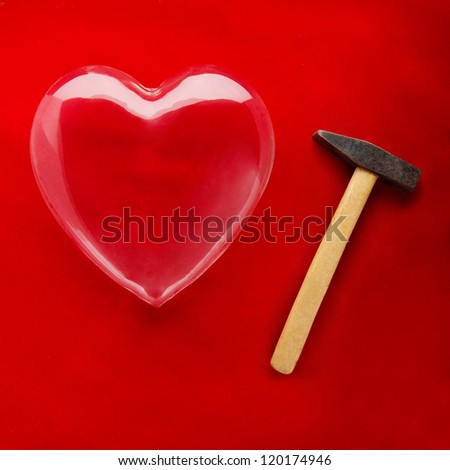 A glass heart and a hammer ready to break it symbolizing fragility