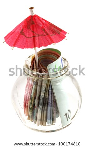 A glass jar contains money : paper currency with red umbrella, isolated on white - Saving for the rainy day - stock photo