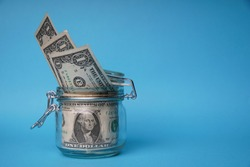 A glass jar full of dollars between one dollar bills. An easy way to save real money. Blue background. Bank image and photo.