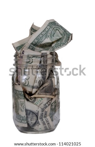 A glass jar stuffed with dollar bills.  Isolated on white.