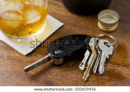 A glass of alcohol on top of a bar table along with a set of car keys.