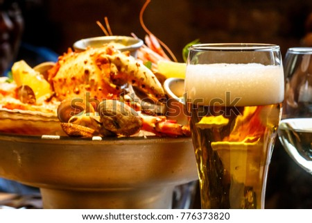 A glass of beer in the background is a plate of crab, shrimp, scallops, lobsters in the restaurant