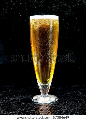 A glass of beer isolated against a black background