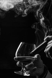 a glass of brandy and cigar with smoke in the male hands. black and white photo