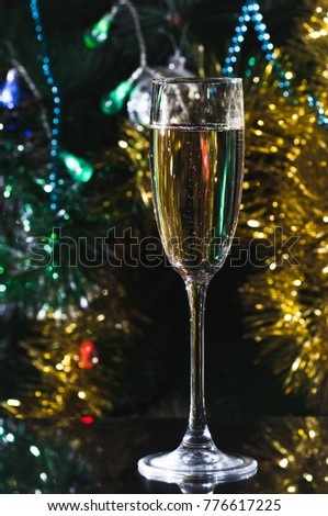 a glass of champagne on the background of a new-year tree #776617225
