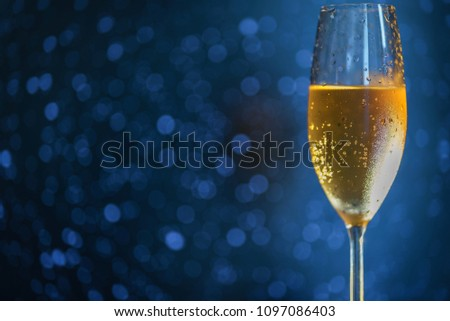 A glass of champagne on the right side of the frame on a blue blurred background #1097086403