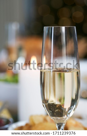 A glass of champagne sitting on a dinner table
