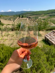 A glass of Chianti wine in front of Tuscany landscape.
