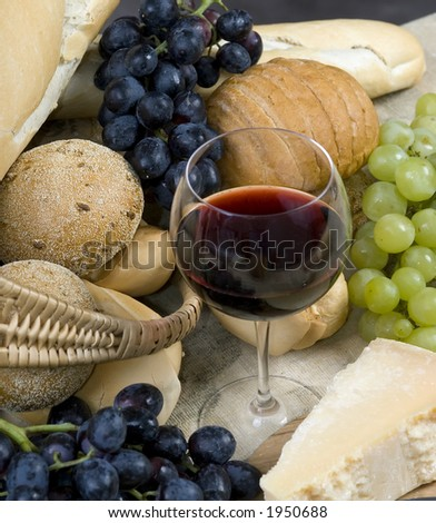 A glass of Chianti wine with assorted breads, cheese and grapes