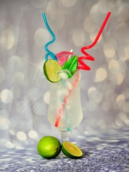 A glass of citrus juice with a slice of lime, ice, straws and an umbrella on a gray shiny background. Close-up.