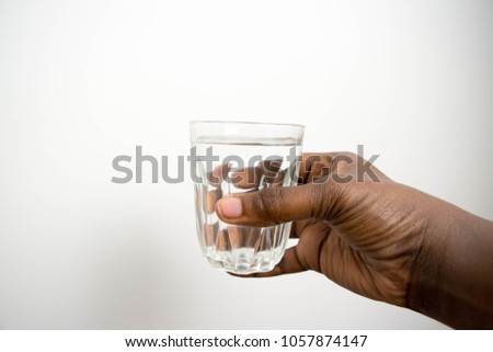 A glass of clean clear mineral water in woman's African American hands. Concept of environment protection, healthy drink hand holding a Glass of pure water isolated on white background