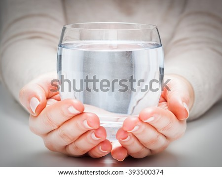 A glass of clean mineral water in woman\'s hands. Concept of environment protection, healthy drink.