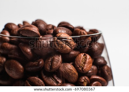 A glass of coffee filled with grains to the top #697080367