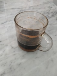A glass of coffee left over from yesterday afternoon is left on the marble table