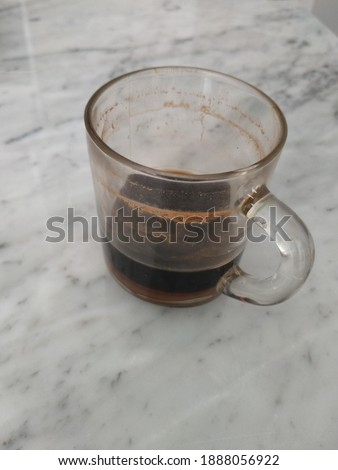 A glass of coffee left over from yesterday afternoon is left on the marble table ストックフォト ©