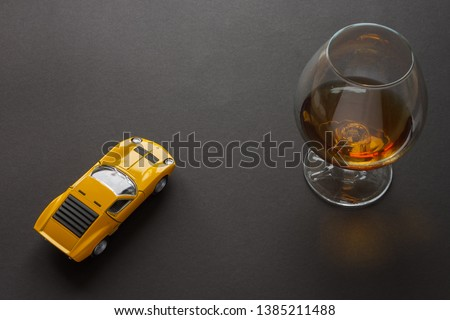 Photo of A glass of cognac and a metal toy sports car of yellow color. Still life. Dark background