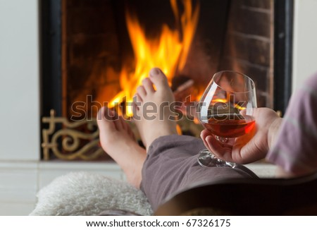 A glass of cognac on the background of a burning fireplace with a brass openwork lattice