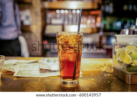 A glass of coke and ice is served at the bar