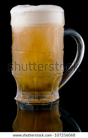 A glass of cold beer on a black background.
