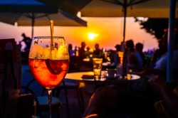 A glass of cold orange cocktail at the sunset on the table of a beach bar at the sunset, with blurry people around having refreshments or partying on a summer evening, with copy space for text