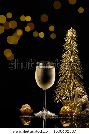 A glass of cold sparkling champagne wine and candy on a festive table decorated with a golden Christmas tree on New Year's Eve 2020.