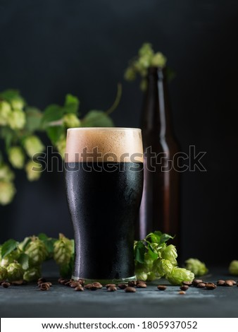 A glass of dark beer, craft stout or porter with green hop cones and coffee Сток-фото ©