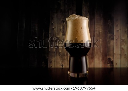 A glass of dark beer on wooden background. Stout or porter with big foam in bar Сток-фото ©