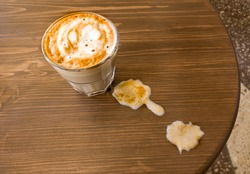 A glass of flat-white coffee stands on the table and next to the visible spilt milk, the view from above