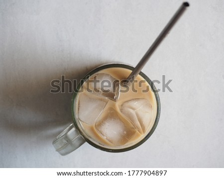 A glass of fresh iced coffee with stainless steel drinking straw. Top view angle. Isolated on white background Photo stock ©