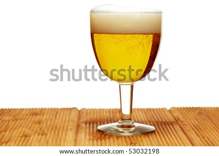 A glass of fresh poured beer in a glass on a wooden table