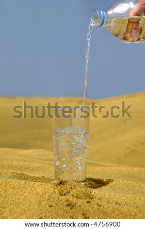 A glass of fresh water and bottle in a desert. Note that the water and bubbles are in motion blur.