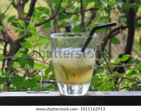 """A glass of freshly prepared rum-based cocktail """"Ti Punch"""" (Petit Punch) with a black straw in a garden setting in Mauritius Island"""