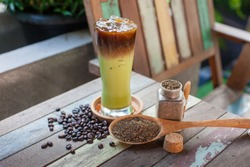 A glass of ice tea with tea powder and black coffee, tea powder in bottle and spoon, Iced green milk tea with hot coffee, coffee beans, two layer drink, mix drink.