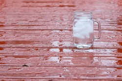 A glass of ice water on a wooden background in the rain