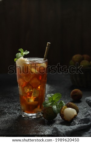 A Glass of Iced Lychee Tea with full ice cube and fresh lychee fruit for topping with kint leaf put on the table Stock fotó ©