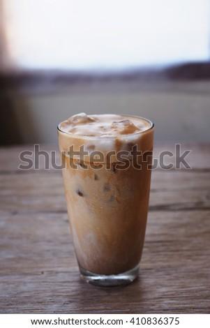 A glass of iced milk coffee with foam. #410836375