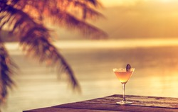 A glass of margarita cocktail on a beach cafe table on a tropical island