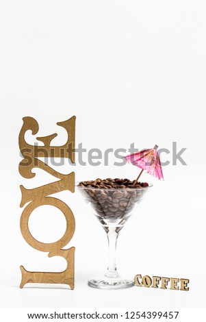 A glass of martini and grains of aromatic coffee and the inscription love and the inscription of coffee with an umbrella  #1254399457