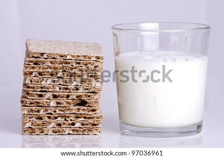 A glass of milk and a slice of crunchy bread for diet.
