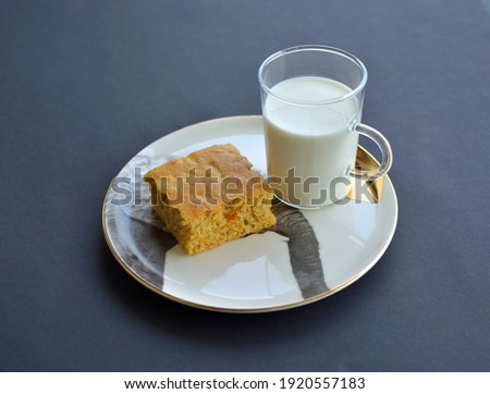 a glass of milk with a slice of homemade cake. Stock fotó ©