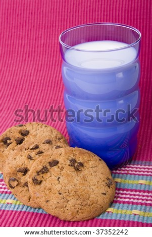 A glass of milk with chocolate cookies on a pink background