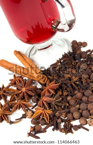 a glass of mulled wine with spices on a white background