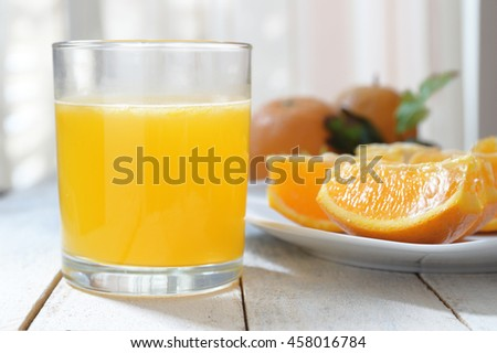 Shutterstock A glass of natural oranges served next to some slices on a white wooden table.