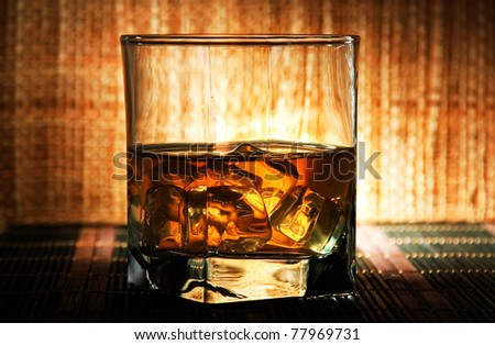 A glass of old whiskey on the rocks.