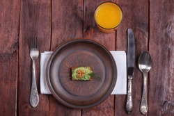 A glass of orange juice, a plate of canapes and cutlery. Canapes with paste of avocado. A tiny portion, anorexia. Eating disorders, poor nutrition. A strict diet. Plate and cutlery