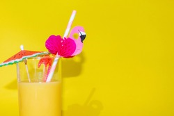 A glass of orange juice in the bottom left corner, with an umbrella and paper flamingo straw, on a bright yellow background