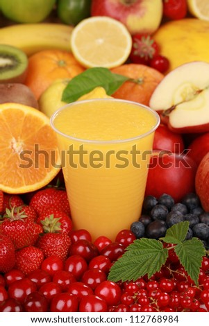 A glass of orange juice surrounded by fresh fruits
